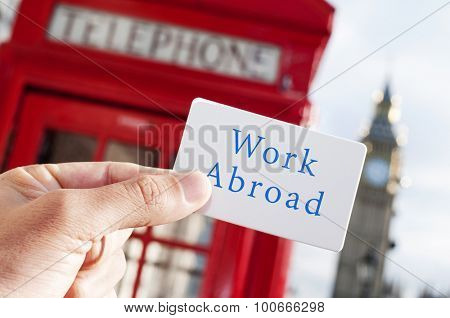 the hand of a young man showing a signboard with the text work abroad, with a red telephone booth and the Big Ben in the background, in London, UK
