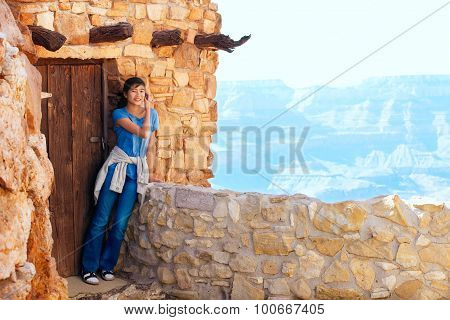 Biracial Teen Girl Relaxing, Leaning Against Rock Wall Overlooking Grand Canyon