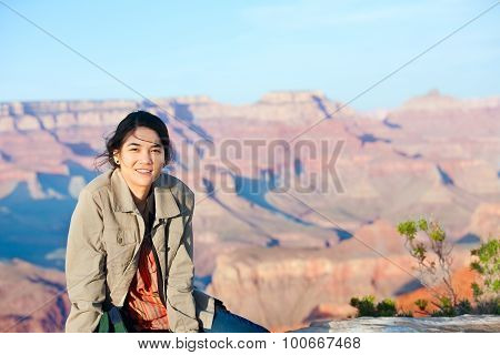 Young Teen Girl Sitting On Rocky Edge At Grand Canyon