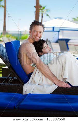 Father Drying Off On Blue Lounger With Disabled Son Off Side Of Pool