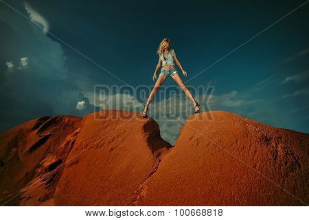 Beautiful woman stay on a peak over the mountains