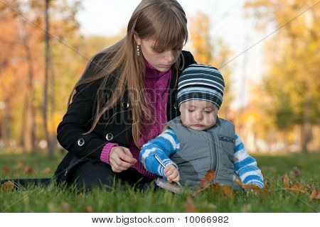 Mom Teaches Her Son In The Autumn Park