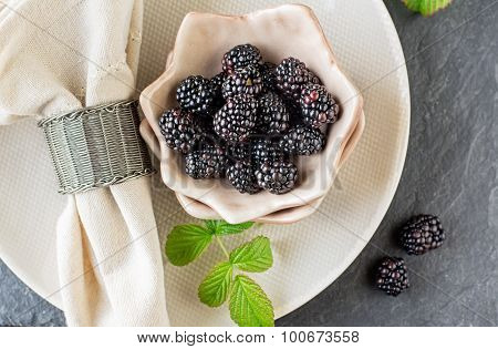 Fresh blackberries for breakfast in ceramic cups portioned