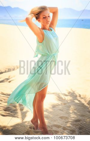 Blonde Girl In Azure Looks Into Camera On Beach