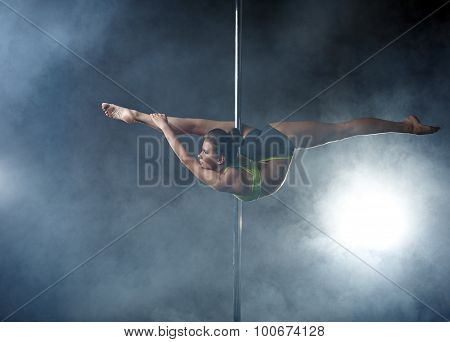 Flexible girl posing in difficult position on pole