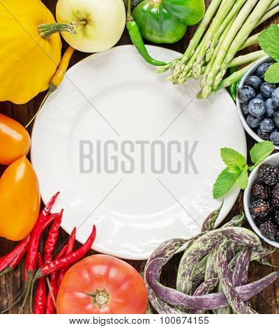 Fruits and vegetables of all colors the rainbow on a wooden table over white plate