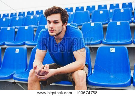 Handsome man athlete sits on chair on a stadium massaging his hand after training