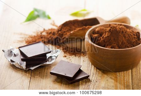 Chocolate Bars And  Wooden Bowl Of Cacao Powder.