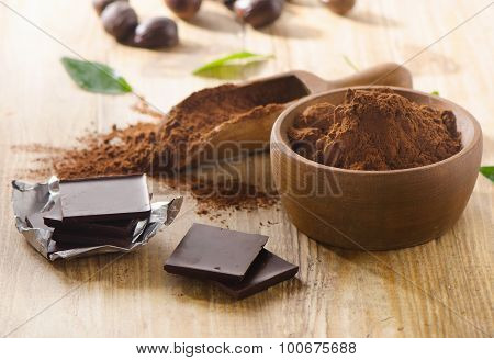 Chocolate Bars And A Wooden Bowl Of Cacao Powder.