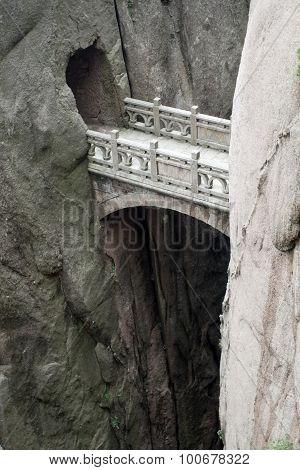 Mountain stone bridge above rocky precipice between the rock