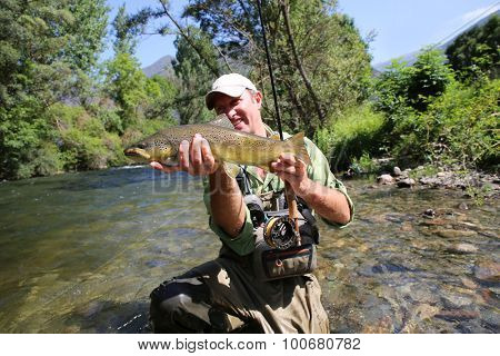 Fly fisherman holding brown trout in stream water