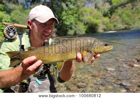 Fly-fisherman holding brown trout recently caught