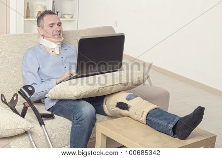Man with leg in neck brace, knee cages and crutches for stabilization and support resting on a sofa with laptop.