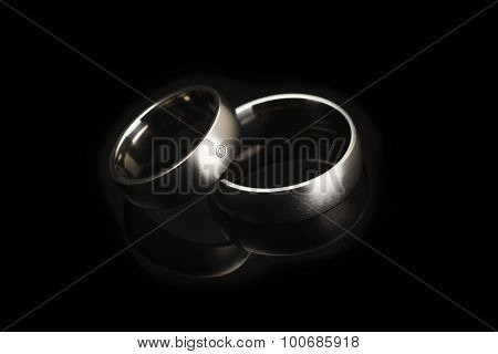 Platinum wedding rings reflected on black surface