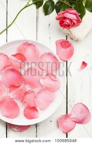 spa concept, pink rose petals in bowl of water with towel and flower on white wood background, high angle view