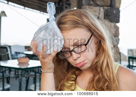 Teenage Girl Puts Ice In A Plastic Bag To The Head