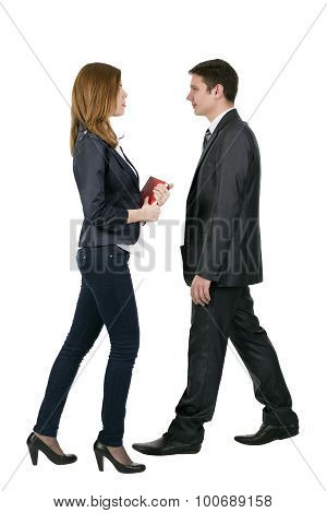 Officially dressed male and female walking towards each other