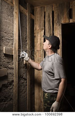 Builder Measures The Height Of The Tape