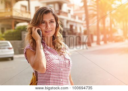 Young Woman Speaking On Cell Phone Down The Street