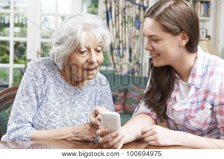Teenage Granddaughter Showing Grandmother How To Use Mobile Phone