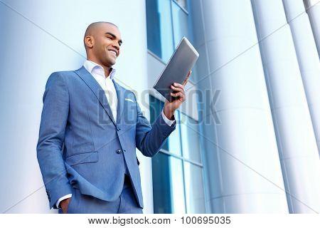 Upbeat businessman standing near column