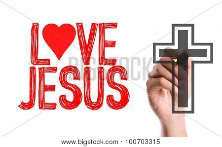 Hand with marker writing the word Love Jesus