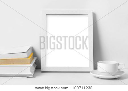 White Desk With Blank Photo Frame, Books, And Coffee Cup
