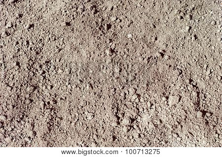 Ground seamless textured surface background under bright sunlight, closeup texture