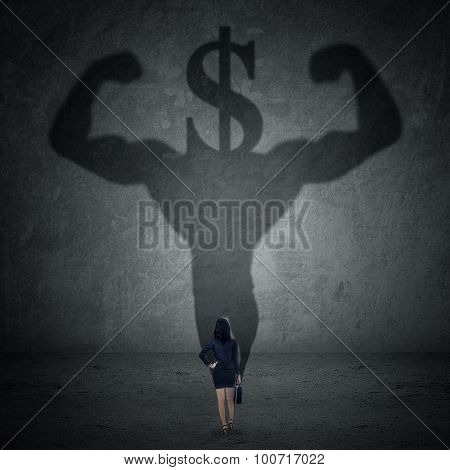 Worker With A Shadow Of Strong Athlete And Dollar Sign