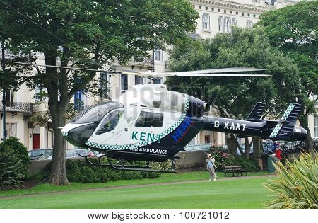 ST. LEONARDS-ON-SEA, ENGLAND - AUGUST 27, 2015: The Kent Air Ambulance takes off from Warrior Square Gardens while attending a medical emergency. The helicopter is a McDonnell Douglas MD902 Explorer.