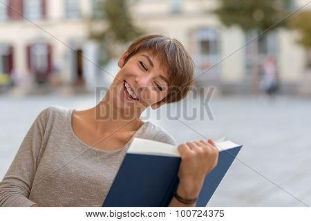 Young Woman Sitting Reading A Book Outdoors