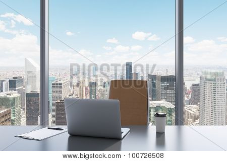 A Workplace In A Modern Panoramic Office With New York View. A Grey Table, Brown Leather Chair. Lapt