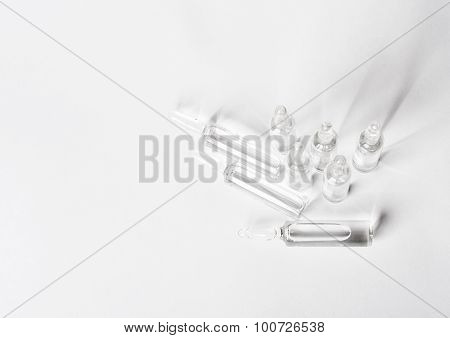 Top View Of Break-seal Glass Ampoule Set With Liquid Medicine On White Background.