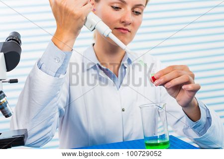 Young female researcher using pipette in medical laboratory