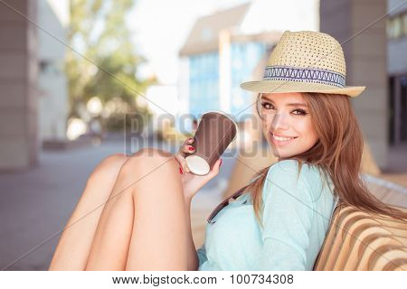 Attractive Young Woman with Cup of Coffee Sitting on the Chair and Smiling at the Camera.