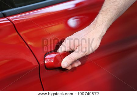 Male hand holding the door handle of red car