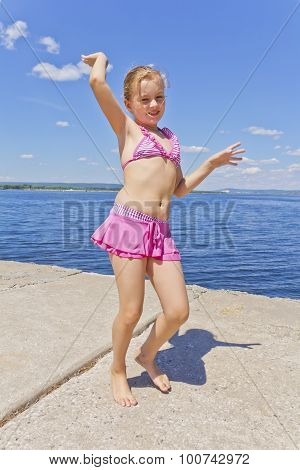 Cute Girl On The Riverbank In Pink Swimsuit