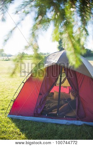 Man resting inside tent on a camping site
