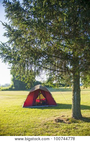 Red tent with man camping on open nature, ontario, canada