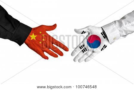 China and South Korea leaders shaking hands on a deal agreement