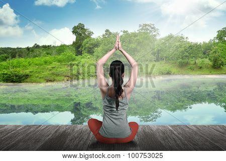 Woman Doing Yoga At The Lake