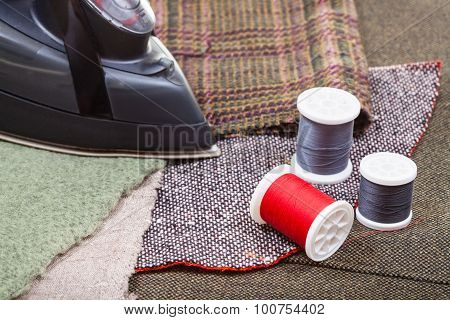 Clothing Iron And Thread Spools On Tissue