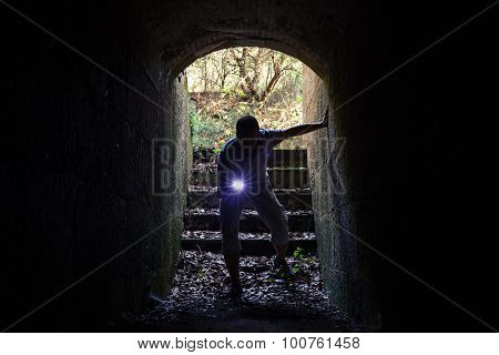Young Man With Flashlight Enters The Stone Tunnel