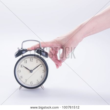Alarm Clock With Hand. Alarm Clock With Hand On The Background.