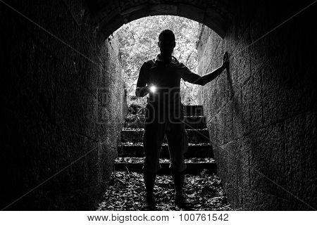 Young Man With A Flashlight In Stone Tunnel