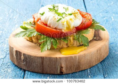 Appetizing Poached Egg On Toast With Tomatoes And Parsley