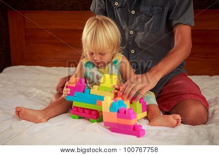 Little Blonde Girl Plays Toy Constructor With Father On Sofa