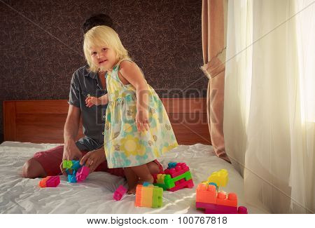 Little Girl Stands By Father On Sofa Among Toy Constructor