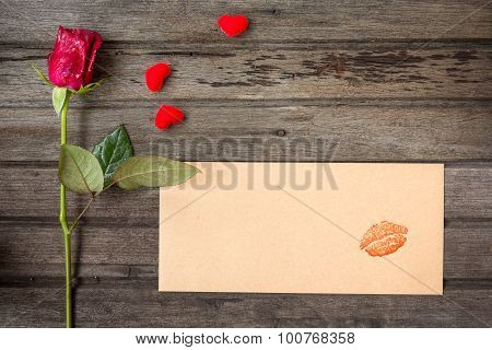 Single Red Rose With Envelope With Kiss And Small Hearts, On Brown Wooden Background, Top View, Vale