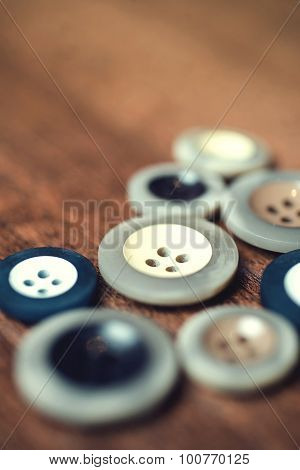 close up, plastic buttons on wood floor background. Selective focus